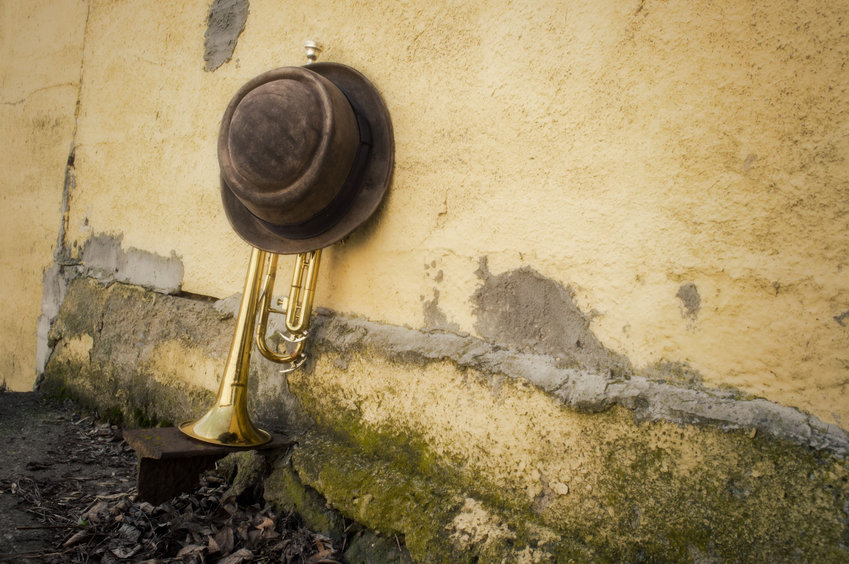 Old worn trumpet against grungy wall with pork pie style top hat