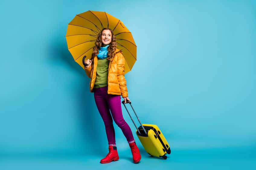 Lady carrying umbrella and travel case