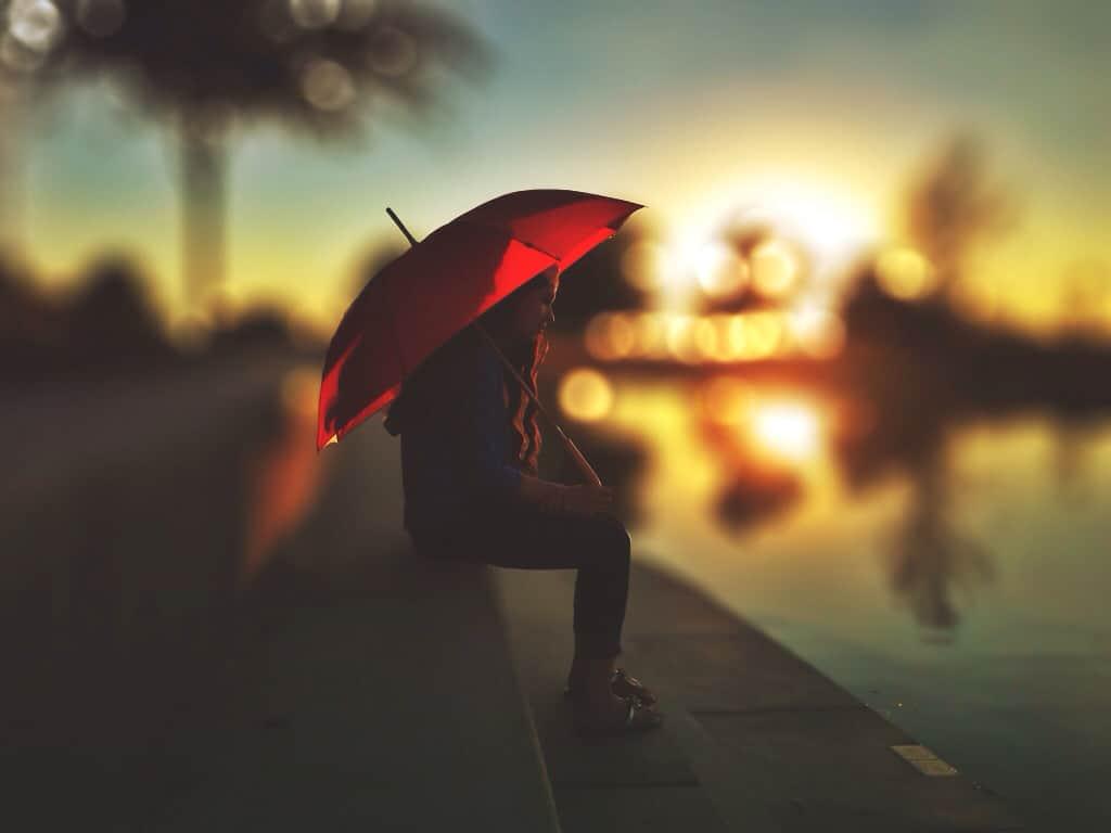 Women sat under a red umbrella
