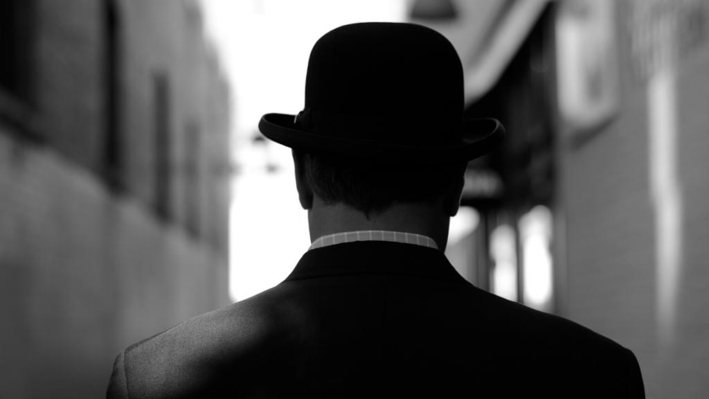 man wearing bowler hat from behind