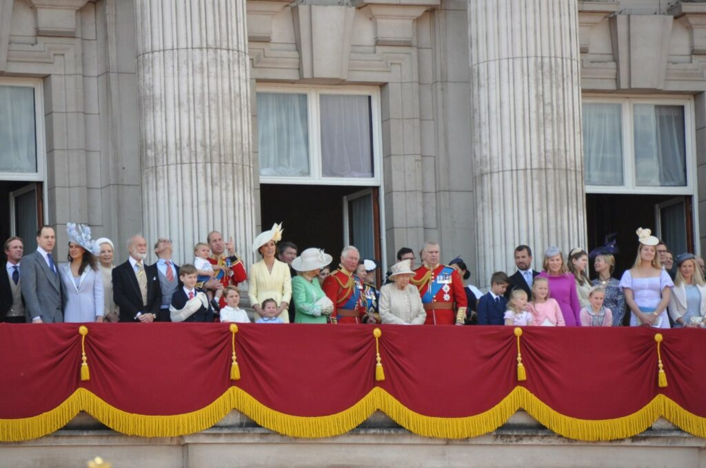 British royals wearing hats on a balcony