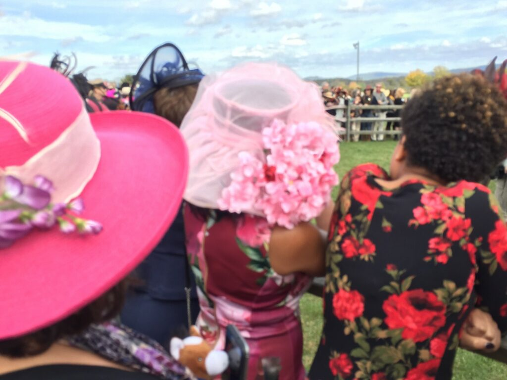 Women wearing hats at horse racing event