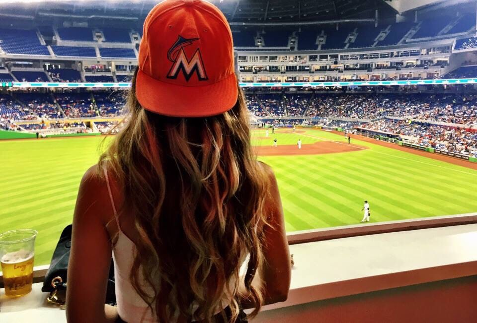 women earring baseball cap at a game with long wavy hair