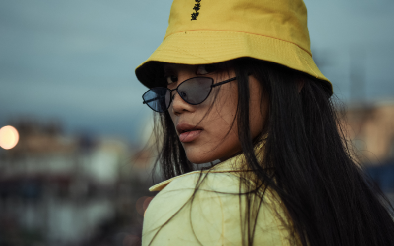 woman wearing a bucket hat with sunglasses