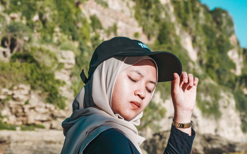 woman casually wearing a baseball cap with a hijab