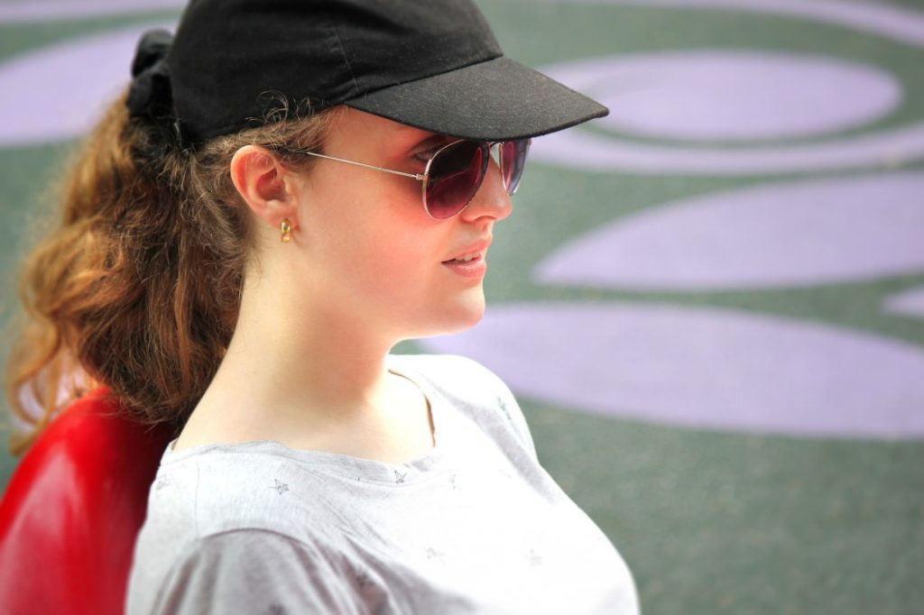 woman wearing sung glasses with baseball cap