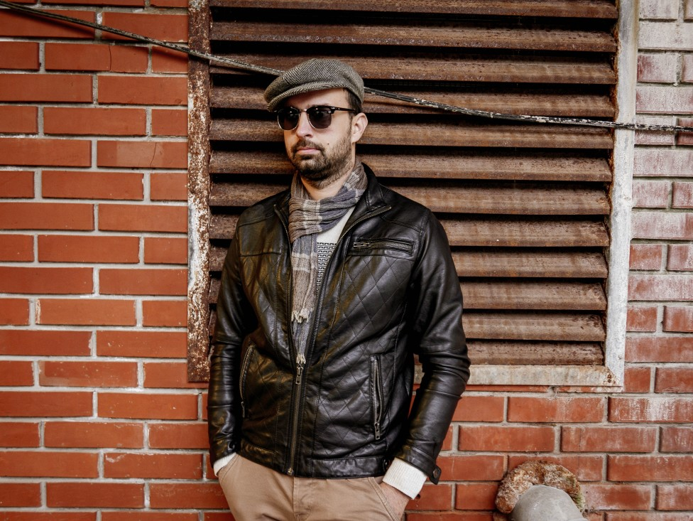 man wearing a flat cap with a leather jacket