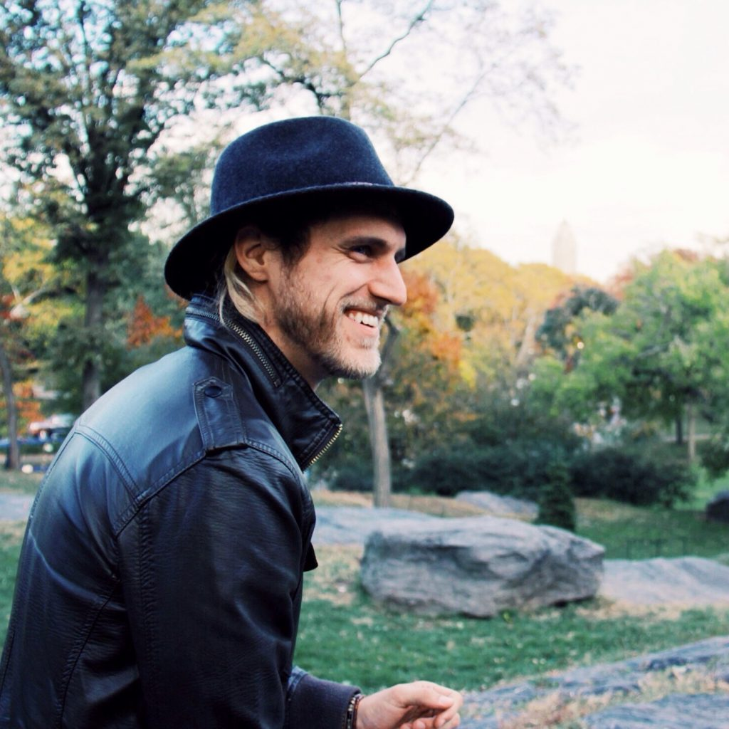 Man wearing a fedora and leather jacket
