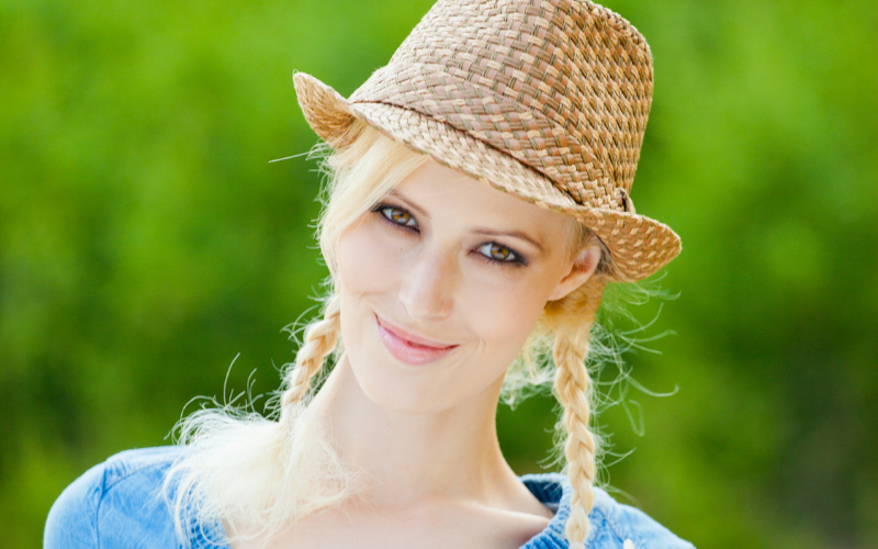 woman wearing braids with a hat