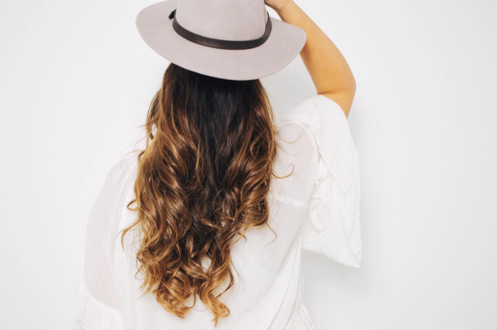 woman wearing long hair with a hat
